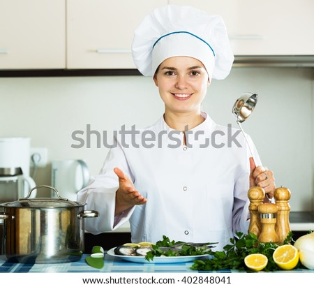 Cheerful woman in cook uniform waiting food to be ready