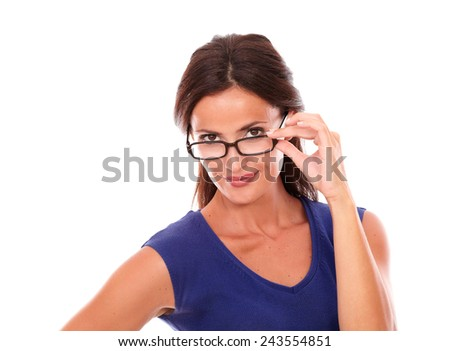 Cheerful woman in purple dress looking over spectacles while smiling in white background - stock photo