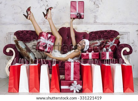 Cheerful woman in santa claus hat with present box lying with legs up on couch christmas time