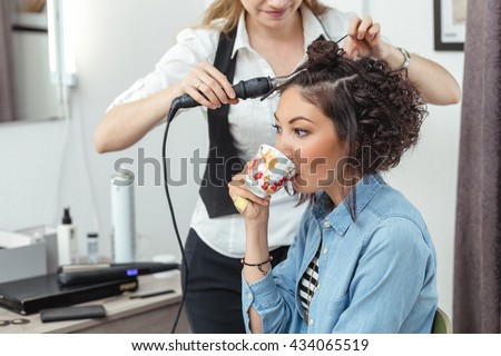 cheerful woman in the Barber shop with beautiful unusual curly hair drinking coffee or tea.