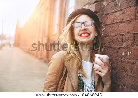 Cheerful woman in the street drinking morning coffee in sunshine light - stock photo