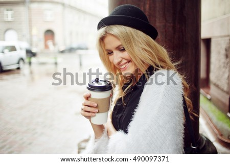 Cheerful woman in the street drinking morning coffee. Walking girl