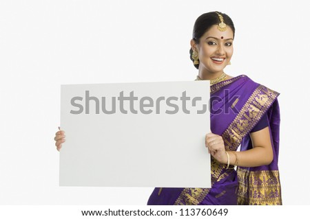 Cheerful woman in traditional Assamese mekhla holding a blank placard and smiling - stock photo