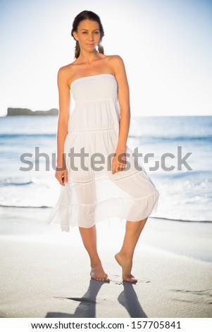 Cheerful woman in white summer dress posing on the beach at dusk