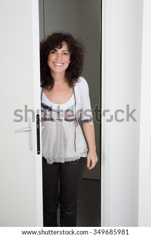Cheerful woman inviting people to enter in home - stock photo