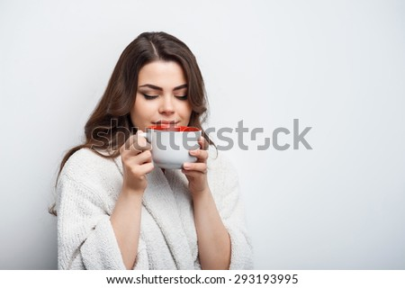 Cheerful woman is holding cup and inhaling the aroma of the brew. She closes her eyes in admiration. Isolated on a grey background and there is copy space in the right side - stock photo