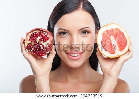 Cheerful woman is holding parts of grapefruit and pomegranate near her face. She is looking at the camera with joy and smiling. Isolated on background - stock photo
