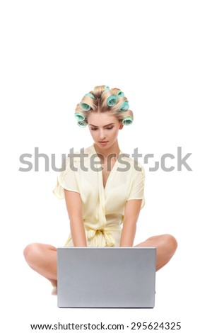 Cheerful woman is looking at notebook with interest. She is wearing bathrobe and curlers in her hair. Isolated on background - stock photo
