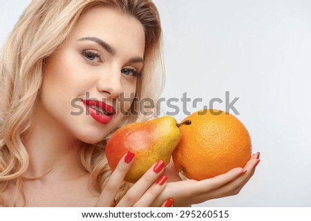 Cheerful woman is presenting yellow pear and orange in her hands. They are joined together. She is smiling. Isolated on background and there is copy space in left side - stock photo