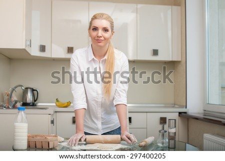 Cheerful woman is rolling dough with rolling pin. She is standing and smiling gently. There is copy space in right side - stock photo