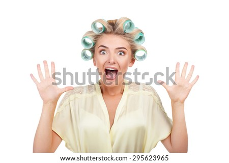 Cheerful woman is screaming and shocked. The lady is raising her arms up with great fear. She has curlers in hair. Isolated on background - stock photo