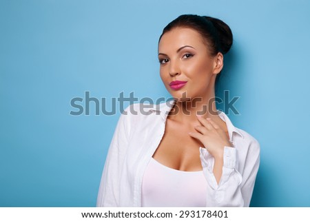 Cheerful woman is self-confident and attractive. She is looking at the camera flirtingly. She is touching her hand to her neck. Isolated on blue background and there is copy space in left side - stock photo