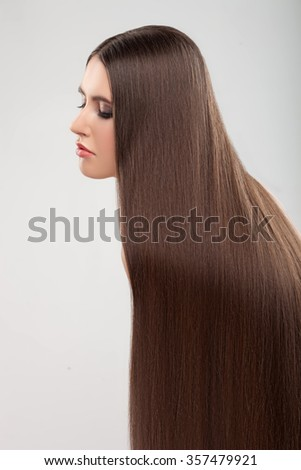 Cheerful woman is showing her long straight healthy brown hair. She is standing and posing. Her eyes are closed with temptation. Isolated - stock photo