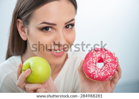 Cheerful woman is showing to the camera apple and donut. She should choose one of them. The lady is smiling. Isolated on a white background - stock photo