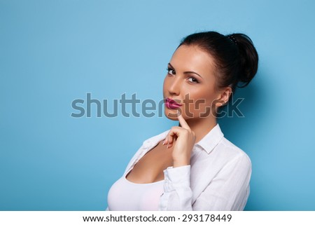 Cheerful woman is thinking carefully about something. She is touching her finger to her chin. Isolated on blue background and there is copy space in left side - stock photo