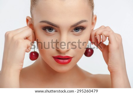 Cheerful woman is touching two cherries to her ears. She is looking at the camera with desire and temptation. Isolated on background - stock photo