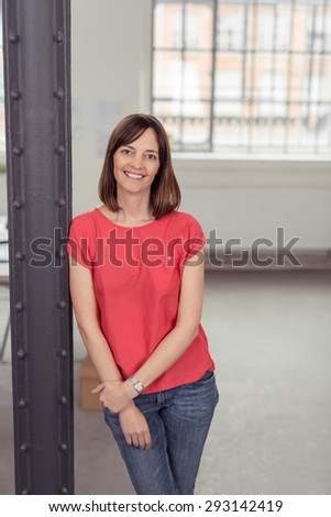 Cheerful Woman Leaning Against Metal Post Inside the Building While Holding her Arm In front her Body and Looking at the Camera. - stock photo
