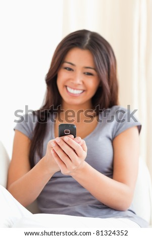 cheerful woman looking at mobile phone in living room
