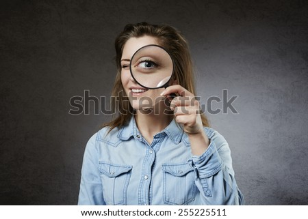 Cheerful woman looking through magnifying glass - stock photo