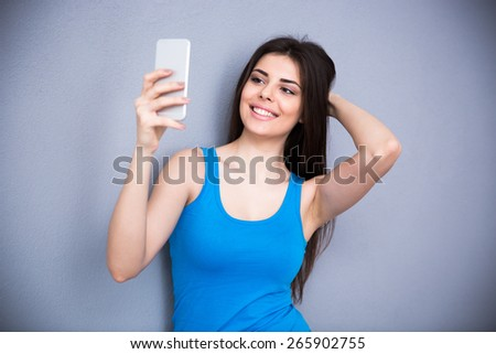 Cheerful woman making selfie photo on smartphone over gray background. Wearing in blue t-shirt - stock photo
