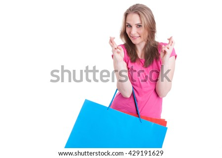 Cheerful woman making wish and luck sign with both hands while holding shopping paper bags with copyspace isolated on white background - stock photo