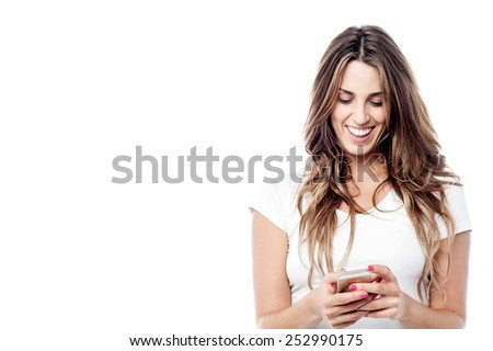 Cheerful woman messaging from her cellphone - stock photo