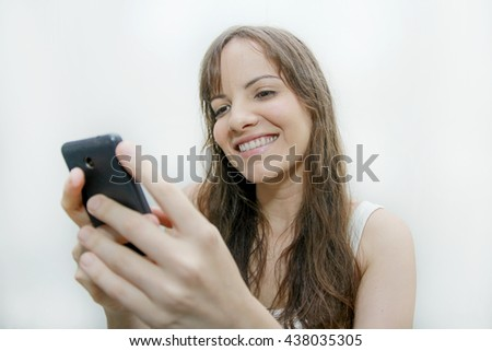 Cheerful woman messaging from her cellphone