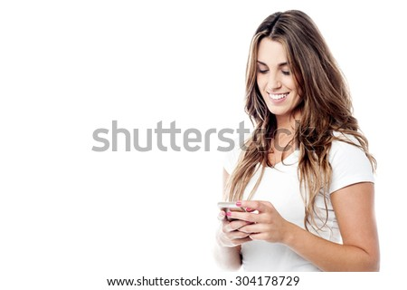 Cheerful woman messaging via her phone - stock photo
