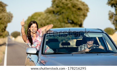 Cheerful woman on car travel doing thumbs up gesture. Happy brunette girl enjoying freedom on roadtrip vacation. - stock photo