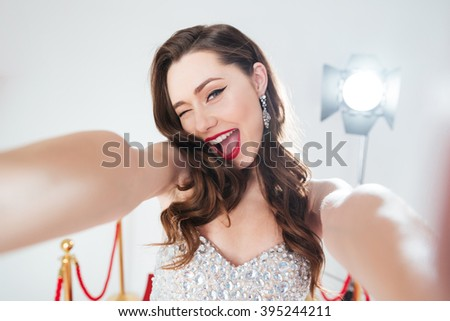 Cheerful woman on red carpet making selfie photo  - stock photo