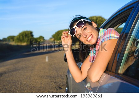 Cheerful woman on summer car travel. Female driver on roadtrip looking at camera and smiling. - stock photo