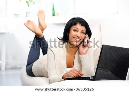 Cheerful woman on the phone in home environment - stock photo