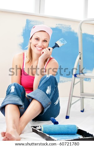 Cheerful woman painting a room in her new house - stock photo