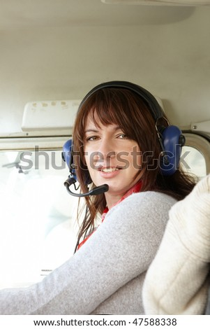 Cheerful woman pilot inside a private aircraft with headset ready to fly. She is sitting on the right seat so she could be instructor, co-pilot or passenger. - stock photo