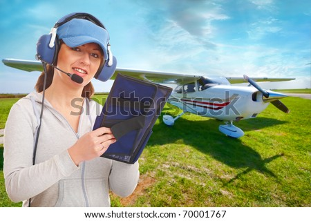 Cheerful woman pilot with headset used in aircraft taking notes on knee-pad, with airplane in the background - stock photo