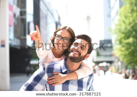 Cheerful woman pointing away while enjoying piggyback ride on man in city - stock photo