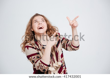 Cheerful woman pointing finger away isolated on a white background - stock photo