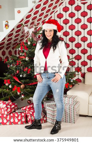 Cheerful woman posing in front of Chrismas tree with gifts home