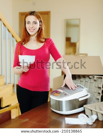 cheerful woman  reading manual for new slow cooker at home interior - stock photo