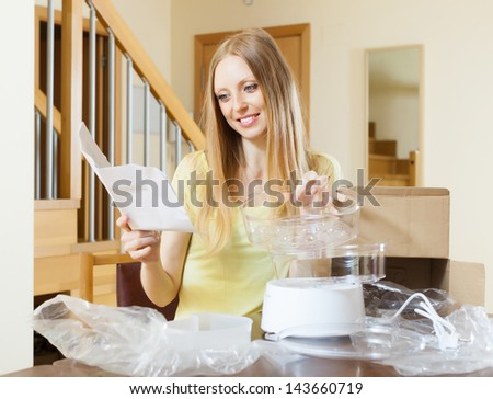 cheerful woman reading user manual for new electric steamer at home
