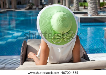 Cheerful woman relaxing at the luxury poolside. Girl at travel spa resort pool. Vacations And Tourism Concept. - stock photo