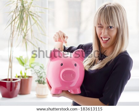 Cheerful woman saving money in piggy bank - stock photo