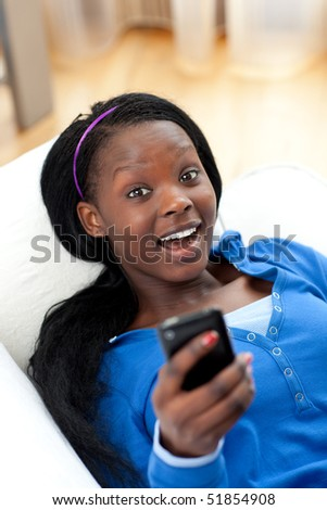 Cheerful woman sending a text lying on a sofa in the living-room - stock photo