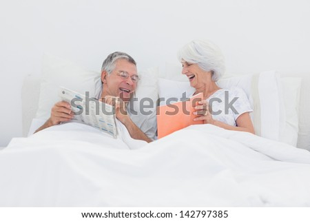 Cheerful woman showing her book to husband in bed - stock photo