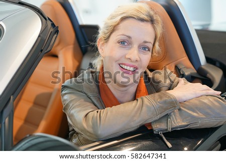Cheerful woman sitting in convertible car