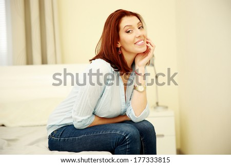 Cheerful woman sitting on the bed at home