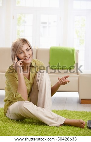 Cheerful woman speaking on mobile phone, sitting on living room floor, gesturing with hand. - stock photo