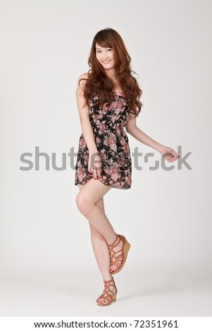 Cheerful woman standing and posing on studio gray background. - stock photo