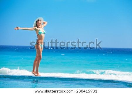 Cheerful woman standing with white hat in striped swimsuit on the ocean coast during holidays summer time - stock photo