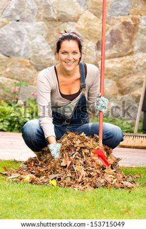 Cheerful woman sweeping leaves fall pile backyard housework outdoor - stock photo